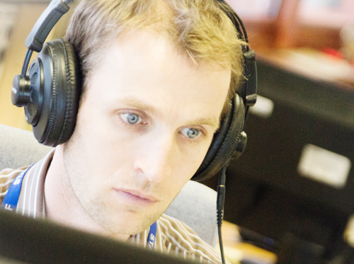 Man concentrating on a computer with headphones on